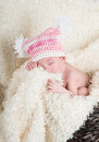 Beautiful newborn baby wearing a pink hat with white pom poms sleeping in brown woven basket on soft cream colored blanket Royalty Free Stock Photography