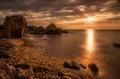 Beautiful ocean sunrise - calm sea and boulders stone coastline Royalty Free Stock Photo