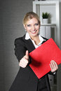 Beautiful office worker giving thumbs up stylish young female holding a red folder a gesture with a big cheerful smile Royalty Free Stock Photo