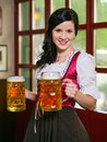 Beautiful oktoberfest waitress with beer photo of a female wearing traditional dirndl and holding huge beers in a pub Royalty Free Stock Photography