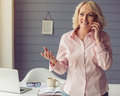 Beautiful old woman in classic shirt is talking on the mobile phone looking away and smiling while standing near her working place Royalty Free Stock Photo