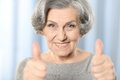 Beautiful old woman showing thumbs up on a blue background Royalty Free Stock Photography