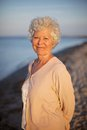 Beautiful old woman standing alone at the beach portrait of senior caucasian lady relaxing outdoors Stock Photo