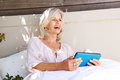 Beautiful older woman with tablet laughing outdoors Royalty Free Stock Photo