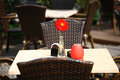 Beautiful open air summer restaurant tables with red flower in vase and chairs served Royalty Free Stock Photo