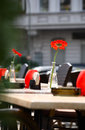 Beautiful open air summer restaurant tables with red flowers in vases and chairs served Stock Image