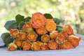 Beautiful orange bouquet of roses on wooden table Royalty Free Stock Photo