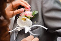 Beautiful orchid boutonniere on groom suit and rose or tuxedo woman s hands Stock Photography