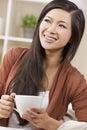 Beautiful Oriental Woman Drinking Tea or Coffee Royalty Free Stock Photo