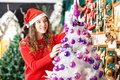 Beautiful owner decorating christmas tree at store female in santa hat Royalty Free Stock Photos