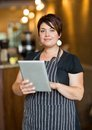Beautiful owner holding digital tablet in portrait of female while standing cafeteria Stock Photos