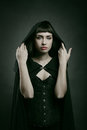 Beautiful pale woman with black cloak dark fantasy and halloween Royalty Free Stock Photo