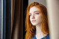 Beautiful pensive woman looking away and dreaming closeup of young tender with long red hair Royalty Free Stock Photo