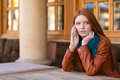Beautiful pensive woman talking on cell phone in outdoor cafe Royalty Free Stock Photo