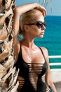Beautiful phenomenal stunning elegant luxury sexy blonde model woman with perfect body wearing a eyewear,sunglasses stands with el Royalty Free Stock Photo