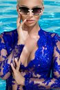 Beautiful phenomenal stunning elegant luxury blonde model woman with perfect face wearing a sunglasses stands with elegant sw Royalty Free Stock Photo