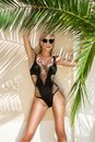 Beautiful phenomenal stunning elegant sexy blonde model woman with perfect face wearing a sunglasses stands with elegant erotic sw Royalty Free Stock Photo