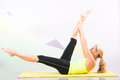 Beautiful pilates instructor with yellow yoga mat fit young blonde showing different exercises basic sport equipment including Royalty Free Stock Photography