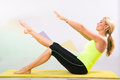 Beautiful pilates instructor with yellow yoga mat fit young blonde showing different exercises basic sport equipment including Stock Images