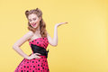 Beautiful pin up girl is presenting something interesting portrait of pretty young woman showing and raising her arms sideways she Royalty Free Stock Photo