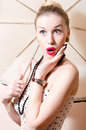 Beautiful pinup blond woman with white umbrella looking aside surprised portrait Stock Photo