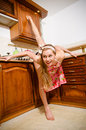 Beautiful pinup woman doing splits in kitchen happy smiling Royalty Free Stock Photography