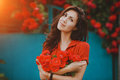 Beautiful portrait of sensual brunette woman holding red roses. Toned image