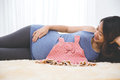 Beautiful pregnant asian woman laying on the bed with a baby gir Royalty Free Stock Photo