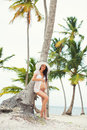 Beautiful pregnant girl in white dress and wide-brimmed hat on beach near palm trees Royalty Free Stock Photo