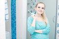 Beautiful pregnant lady holding toothbrush and smiling in her modern bathroom indoor shot Stock Photos