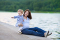 Beautiful pregnant mother and her baby daughter in river shore young little playing on Stock Images