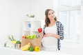 Beautiful pregnant smiling woman in the kitchen eating vegetables Royalty Free Stock Photo