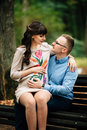Beautiful pregnant stylish couple relaxing outside in the autumn park sitting on bench. Royalty Free Stock Photo
