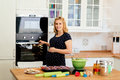 Beautiful pregnant woman baking muffins Royalty Free Stock Photo