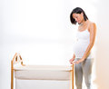 Beautiful pregnant woman dreaming with baby cradle Stock Photography