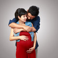 Beautiful pregnant woman and her husband women on grey background Stock Images