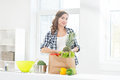 Beautiful pregnant woman in the kitchen with shopping bag and pineapple Royalty Free Stock Photo