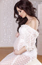 Beautiful pregnant woman with long dark hair wearing lace dress Royalty Free Stock Photo