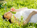 Beautiful pregnant woman relaxing on grass in the spring park Stock Photo