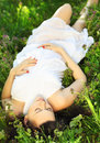 Beautiful pregnant woman relaxing on grass in the spring park Royalty Free Stock Image