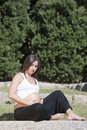 Beautiful pregnant woman relaxing in the park Stock Photo