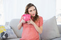 Beautiful pregnant woman shaking a piggy bank sitting on couch in living room Royalty Free Stock Images