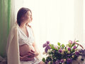 Beautiful pregnant woman sitting near window on and stroking tummy Stock Image