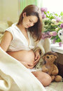 Beautiful pregnant woman sitting on sofa near window and stroking tummy Royalty Free Stock Photo