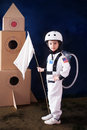 Beautiful preschool boy, dressed as astronaut, with flag and car Royalty Free Stock Photo