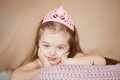Beautiful princess girl in pink dress lying down bored. Royalty Free Stock Photo