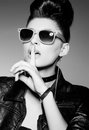 Beautiful punk woman model wearing sun glasses and leather jacket Royalty Free Stock Photo