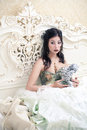 Beautiful queen like girl with statuette of angel vintage portrait a in the white bedroom holding a cupid retro style studio shot Stock Images