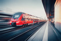 Beautiful railway station with modern red commuter train in motion Royalty Free Stock Photo