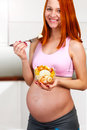 Beautiful red hair pregnant woman eating fruit salad inside kitchen Stock Photography